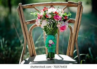 A bridal bouquet with roses, eustoma, berries A bridal bouquet on an ancient chair. Floristic composition.