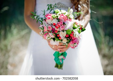 A bridal bouquet with roses, eustoma, berries in the bride's hands. Floristic composition.