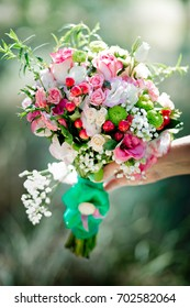 A bridal bouquet with roses, eustoma, berries in the bride's hand. Floristic composition.