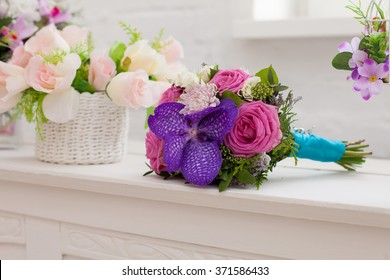 bridal bouquet from roses and an orchid of pink and violet color on a white table
