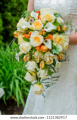 Bridal bouquet of roses and tulips and lilies held by bride.