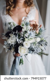 Bridal bouquet. Wedding. The girl in a white dress holds a beautiful bouquet of white, blue, bordeaux flowers and greenery, decorated with long silk ribbon