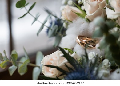 Bridal bouquet and wedding rings on window