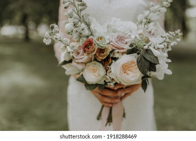 Bridal bouquet with white English roses held by a bride in white dress on green blur background