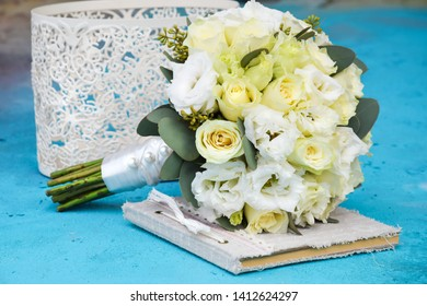 A bridal bridal bouquet of white eustoma flowers and milky-colored roses of the Wendella variety is lying on the book of wedding wishes in a vintage style handmade with lace braid of a white vase
