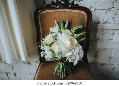 bridal bouquet of white flowers and greenery is on a vintage chair against a white brick wall in loft