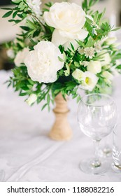 a bridal bouquet of white flowers and greens and glass glasses stand on a table, wedding table setting