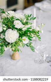 bridal bouquet of white flowers and greens and glass glasses stand on a table, wedding table setting