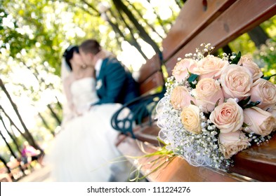 Bridal bouquet of white roses on a bench and blurred newlyweds
