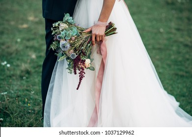 Bridal bouquet of wildflowers with long pink ribbons in bride's hand