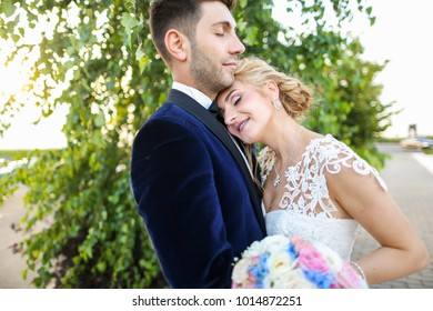 Bridal couple with bouquet of flowers celebrating in the park