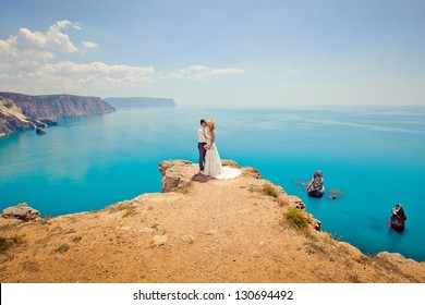 bridal couple man and woman kissing on a cliff