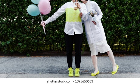Bridal couple walking in a city with a bouquet and balloons, happy bride and groom together.
