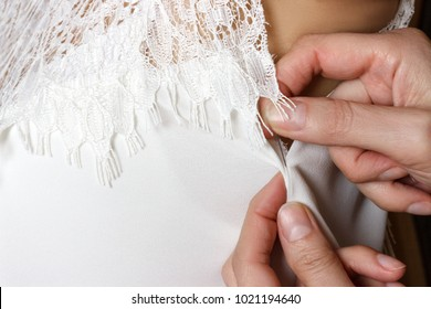 Bridal Gown Fitting. seamstress prepares dress to the fitting.
