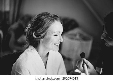 Bridal morning in black and white. Young beautiful bride applying wedding make-up.