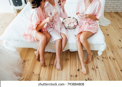 Bridal morning. Bride with bridesmaids drinking champagne in the peignoir.