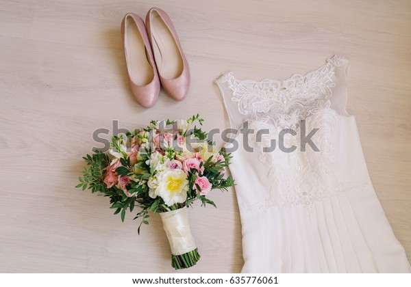 Bridal morning details. Beautiful bouquet of yellow and pink flowers, white wedding dress and leather shoes. Wedding composition, flat lay.