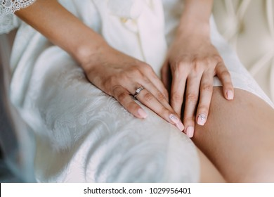 Bridal morning preparation. Wedding ring on bride's hand. Artwork. Selective focus on the wedding ring. Close-up