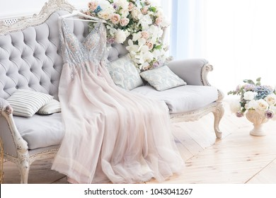 Bridal pink dress gown on the grey classic sofa with flowers and wooden floor