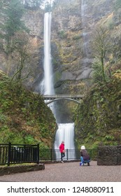 Bridal Veil, OR - December 2, 2018: Female Asian tourist taking photos at beautiful scenic Multnomah Falls in the Columbia River Gorge in the Pacific Northwest.