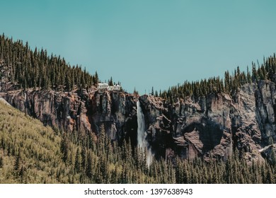 Bridal Veil Falls, the tallest free-falling waterfall in Colorado, surrounded by pine trees. A privately owned, historic power plant sits atop the falls in Telluride, Colorado, USA