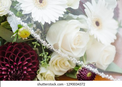 Bridal veil partially covers wedding flowers. Bouquet made up of white roses, white gerberas, and roses
