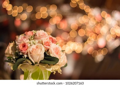 Bridal wedding bouquet in a romantic ambient with warm coloful bokeh lights
