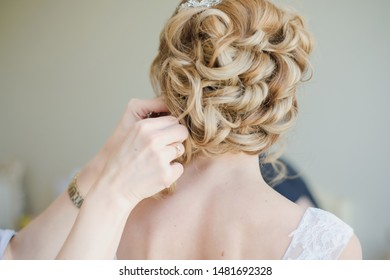 Bridal wedding hairstyle. Tender wedding stylish hairstyle. Elegant bride standing back with collected up do hair. Fine art wedding. Light bridal morning preparation.