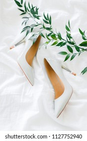 Bridal wedding shoes, wedding details. Wedding floristry,green branch. Luxury classic shoes for bride