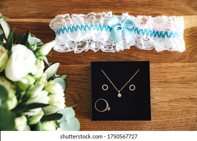 Bride accessories flat lay: black box with golden jewelry, white lace garter with light blue ribbon bow and white wedding bouquet on wooden background