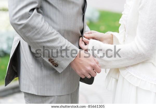 Bride adjusting or fasten groom's suit