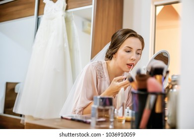 Bride applying lipstick with brushin her wedding day. Focus on her lips.