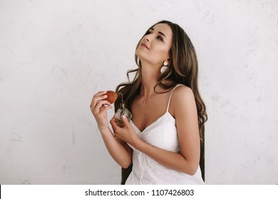 Bride applying perfume. Girl with perfume, young beautiful woman holding bottle of perfume and smelling aroma