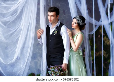 The bride approaching the groom and touching him tenderly from behind. Romantic wedding ceremony decorated in boho and rustic style
