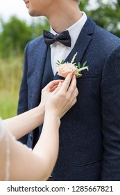 the bride attaches the groom a buttonhole on the lapel of his jacket
