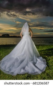 Bride back of her dress at sunset by a lake