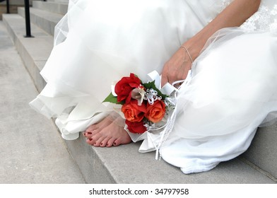 Bride is barefoot on the church steps her feet aching, she lays her bouquet of red and orange roses besides them.