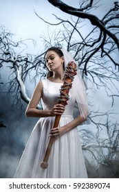 Bride with baseball bat against the dried tree