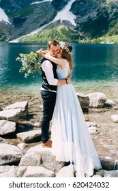 bride with the beautiful blue dress and groom hugging with views of the beautiful green mountains and lake with blue water
