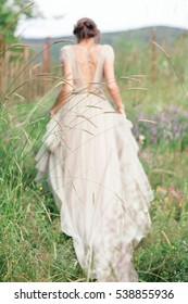 Bride in a beautiful dress with a bouquet of flowers and greener