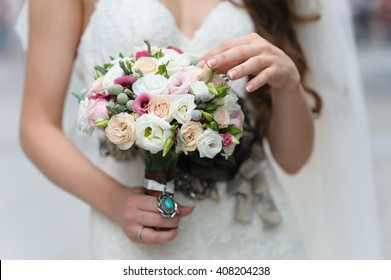 Bride in beautiful dress holding a bouquet of flowers. Bride touches the flowers by hand.