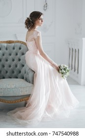 Bride in beautiful dress sitting on a chair with the wedding bouquet. On The Morning Of The Bride. Fine art wedding.