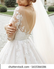 The bride with a beautiful dress that shows her bare back. Portrait of the fashion bride.
