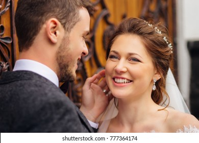 the bride with beautiful jewelry sincerely smiles standing near her husband