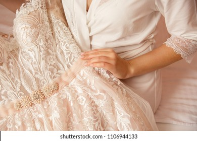 Bride with beautiful manicure holding wedding dress. Wedding preparation of bride.