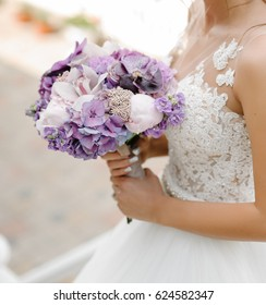 Bride with a beautiful purple wedding bouquet