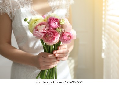 Bride with beautiful ranunculus bouquet indoors, closeup. Space for text