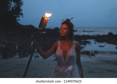 Bride in beautiful wedding dress is holding torchlight on the beach at night