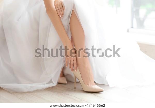 美しいウエディングドレスを着た花嫁が靴を履く