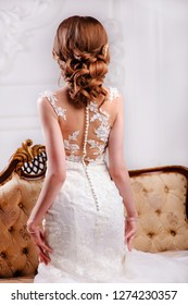 The bride in a beautiful white wedding dress. The view from the back
